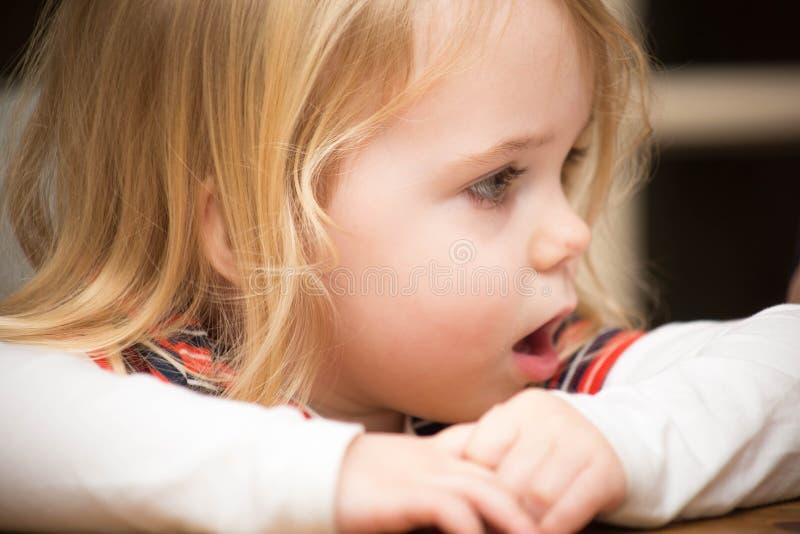 Kinderporträtblicke und auf dem Tisch sitzen lizenzfreie stockfotos