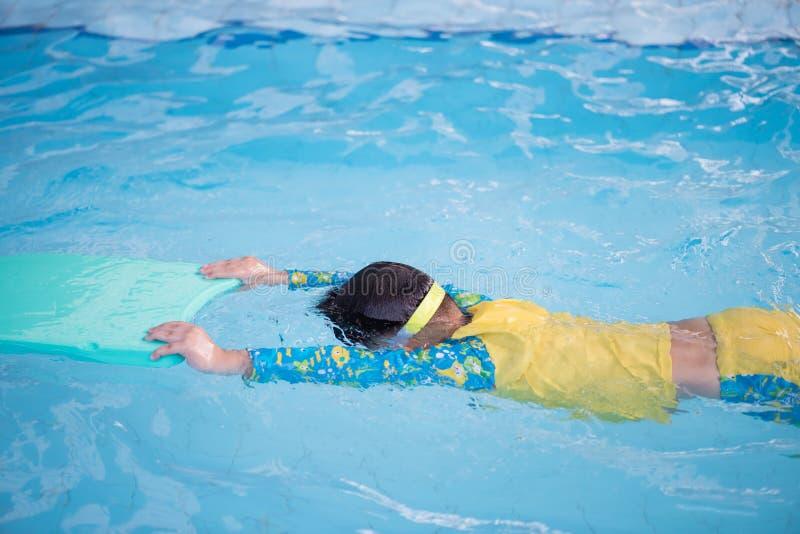 Kinderpraxis, die durch das Schwimmen des Schaums schwimmt stockfotos