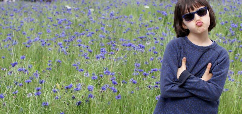 Kinderpult für skeptische Körpersprache, Blumenwiese-Hintergrund stockbild