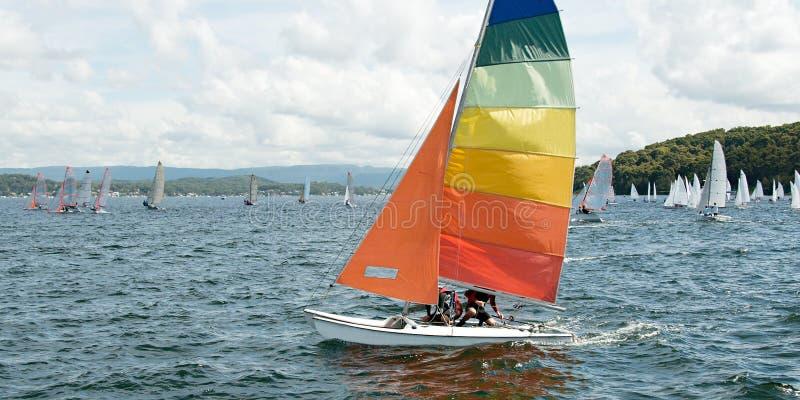 Kinderrennen auf einem kleinen Katamaran-Segelboot mit Farbtupfer lizenzfreies stockbild