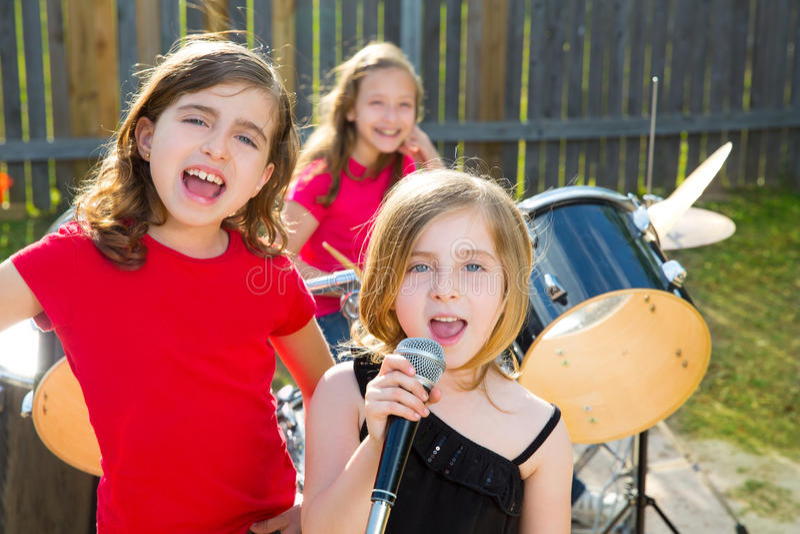 Kindersängermädchen, das Liveband im Hinterhof spielend singt stockbild