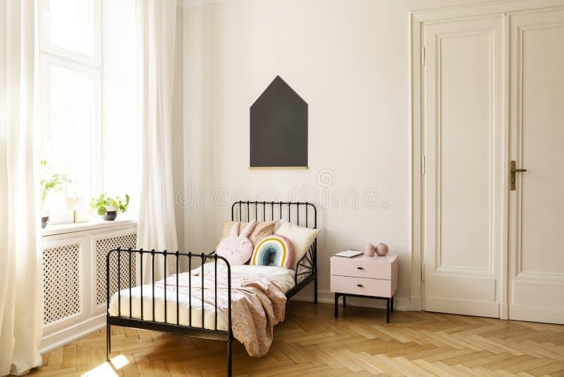 Kinderschlafzimmerinnenraum mit einem Einzelbett, einem Fenster und einer Tafel auf einer Wand lizenzfreies stockbild