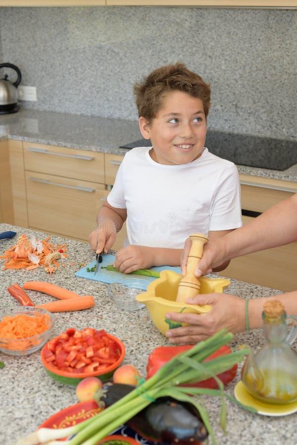 Kinderschnittknoblauch, der das Mittagessen mit einem Erwachsenen und Lächeln vorbereitet lizenzfreies stockbild