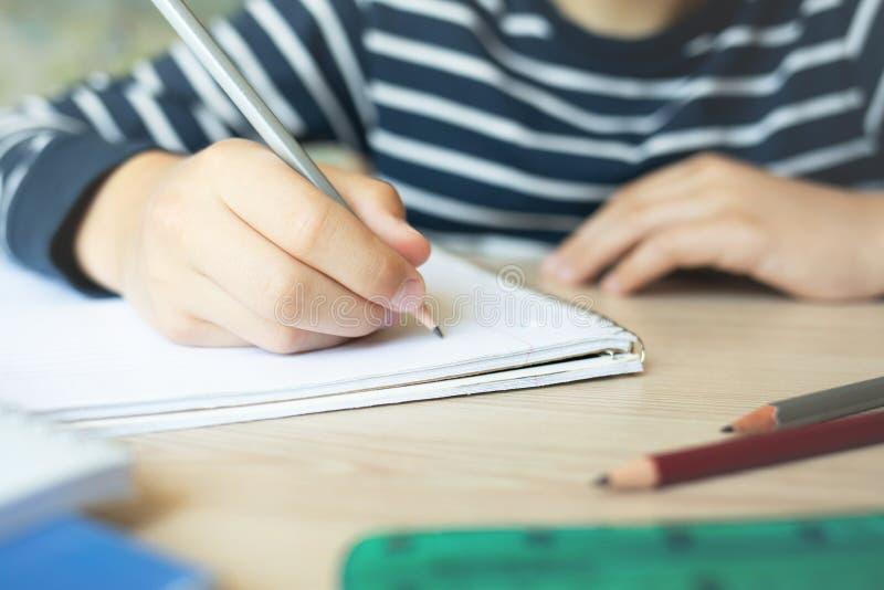 Kinderschreiben im Notizbuch stockfotos