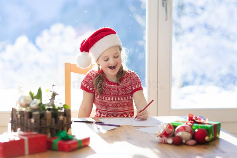 Kinderschreibensbuchstabe zu Sankt auf Weihnachtsabend Kinder schreiben Weihnachten anwesenden Wunschzettel das kleine Mädchen, d stockfoto