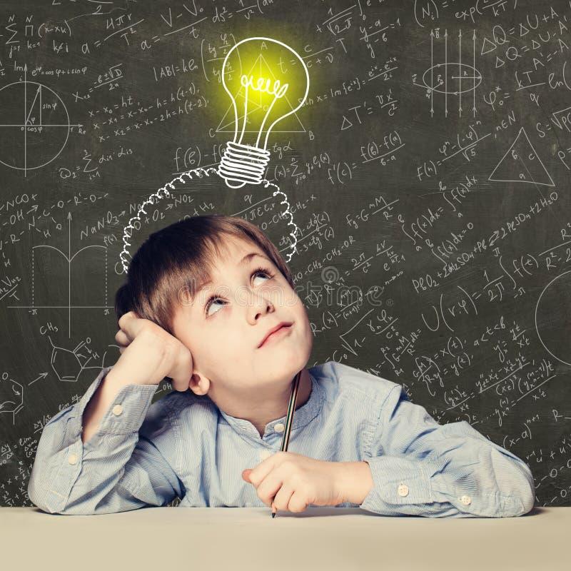 Kinderschuljungenblick auf Glühlampe auf Hintergrund mit Wissenschaftsformeln stockfotos