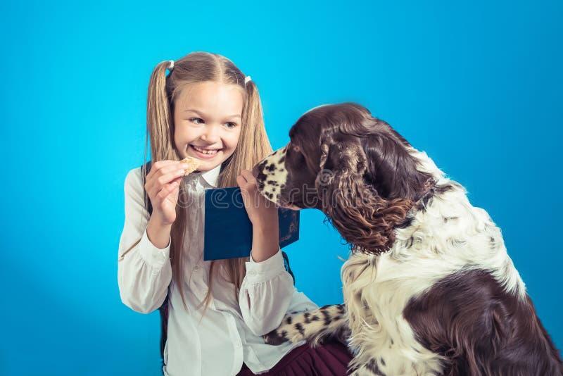 Kinderschulmädchen nehmen ein Buch und spielen mit ihrem Hund auf dem blauen backgroundild Schulmädchen, das ein Buch auf blauem  lizenzfreie stockfotos