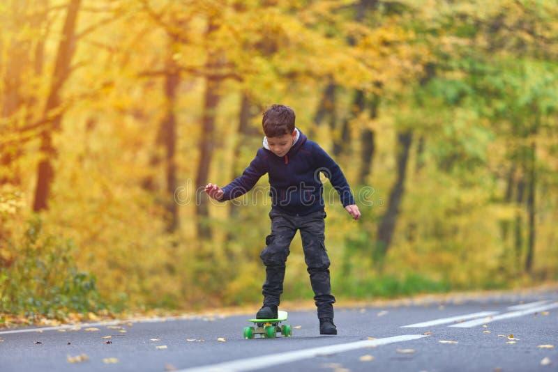 Kinderskateboardfahrer, der Skateboardtricks in der Herbstumwelt tut lizenzfreie stockbilder