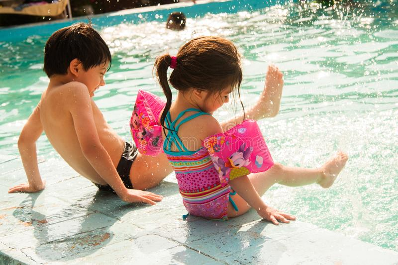 Kinderspiel auf einem Swimmingpool im Sommer stockbild