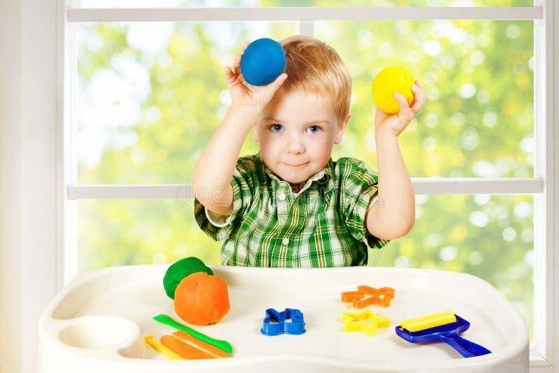 Kinderspiel, das Knetmasse, Kind und bunten Clay Dough, Spielwaren modelliert stockfotografie