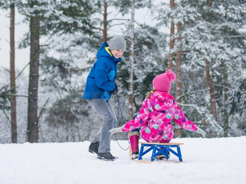 Kinderspiel im Schnee mit Schlitten stockbild