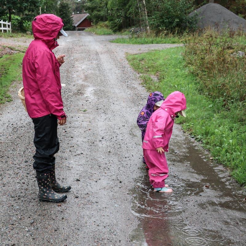 Kinderspiel und Springen in schlammige Pfütze stockbild