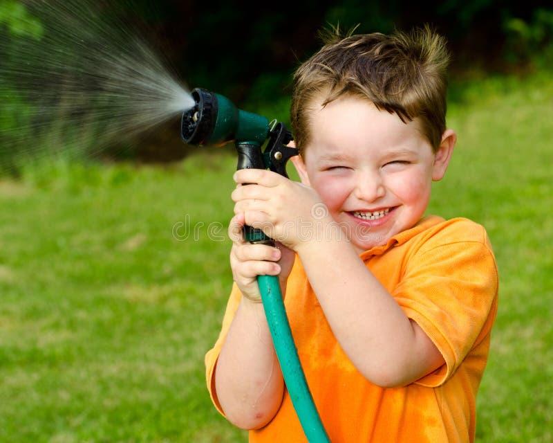 Kinderspiele mit Wasserschlauch draußen lizenzfreie stockbilder