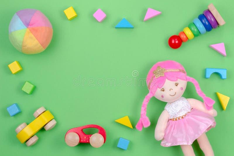 Kinderspielwaren-Hintergrundrahmen mit Spielzeugpuppe, hölzernen Autos und bunten Blöcken auf grünem Hintergrund stockbild