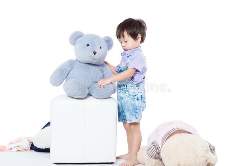 Kinderstand, der mit der Puppe spielt stockfoto