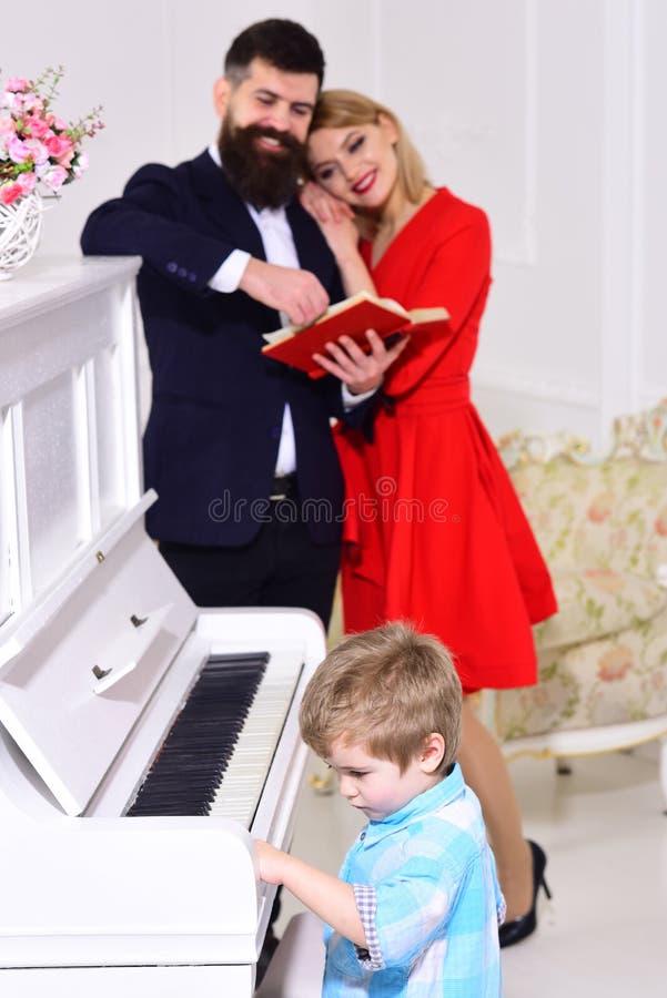 Kinderstand nahe Klaviertastatur, wei?er Innenhintergrund Musikerausbildungskonzept Reiche Eltern genie?en Elternschaft lizenzfreie stockfotos