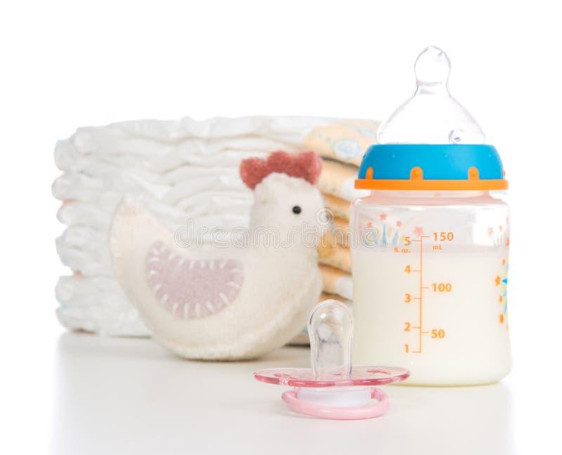 Kinderstapel von Windeln, von Nippel, von Zehe und von Babysaugflasche mit lizenzfreie stockfotos