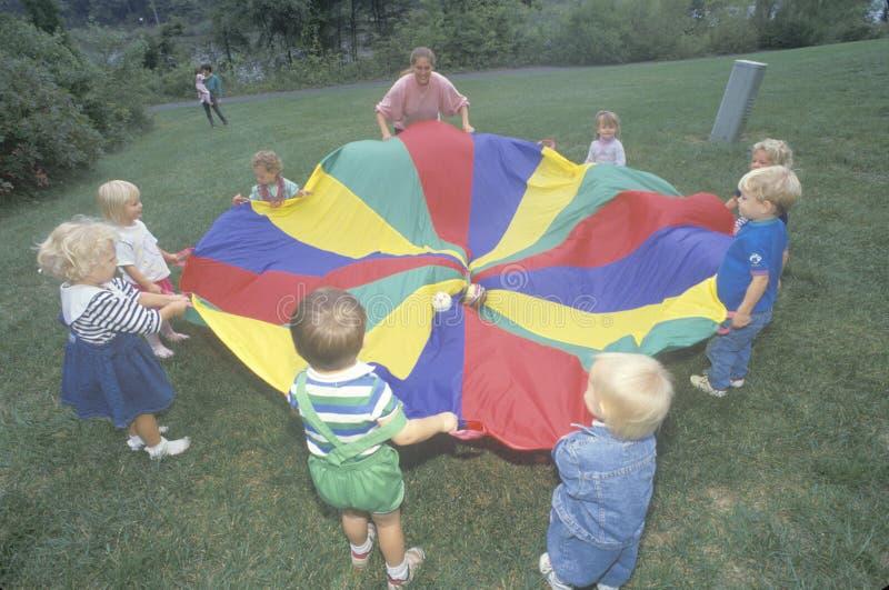 Kindertagesstättenkinder, die ein Fallschirmspiel spielen lizenzfreie stockfotografie
