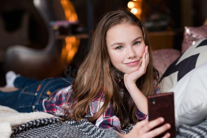 Kindertechnologie-Suchtmädchen, das Telefon verwendet stockbilder