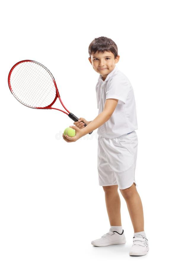 Kindertennisspieler, der einen Ball mit einem Schläger dient stockfotografie