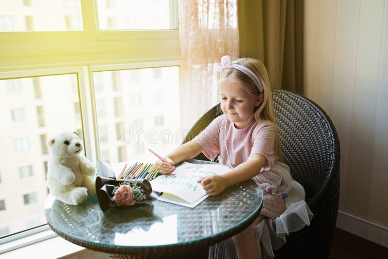 Kindertochter-Malereipostkarte f?r Mutter M?dchen, das zu Hause auf Tabelle, als n?chstes liegende rosa Blume f?r Mutter sitzt Mu lizenzfreies stockbild
