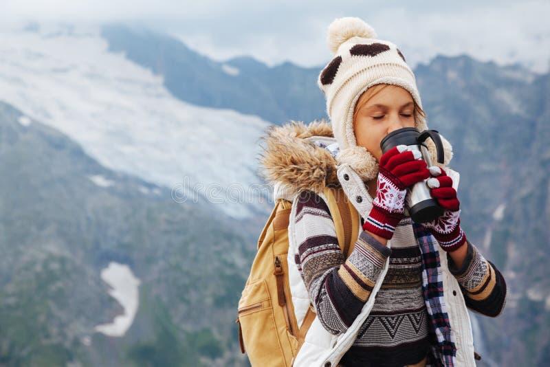 Kindertrinkender Tee in der Thermosflasche in den Bergen lizenzfreie stockbilder