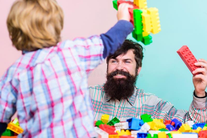 Kinderverzorging en opvoeding r De vaderzoon creeert bouw Vader en jongensfamilievrije tijd vader stock afbeeldingen