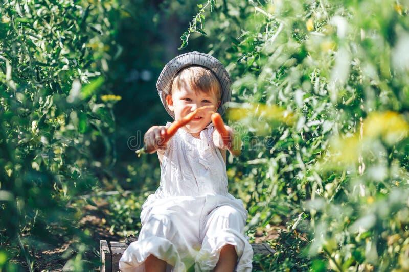 Kinderverzorgster met wortelen en cacual clotherzitting in groen gras stock foto
