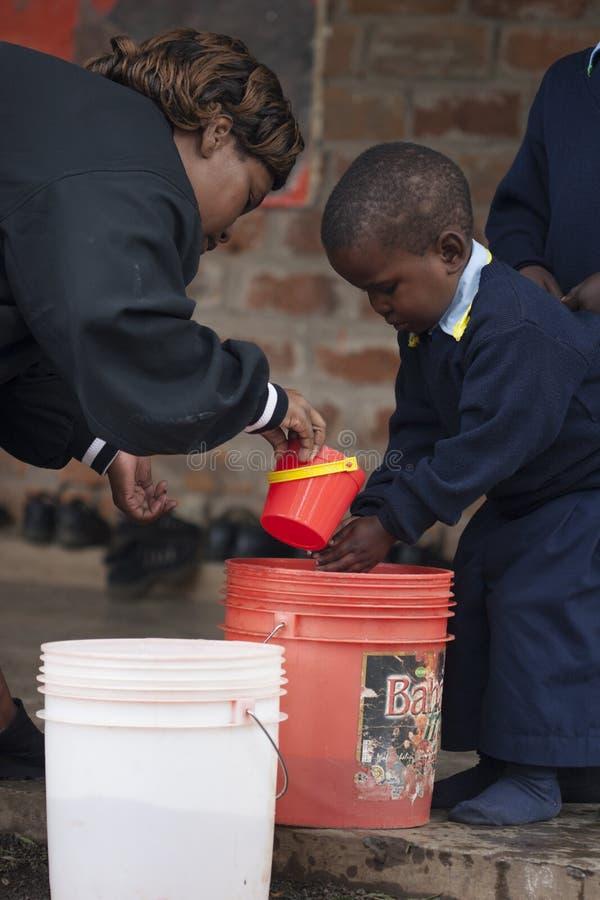 Kinderwaschende Hände in der Schule in Afrika lizenzfreies stockbild
