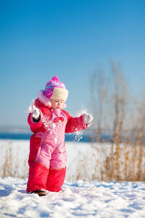 Kinderwerfender Schnee im Winter lizenzfreie stockbilder