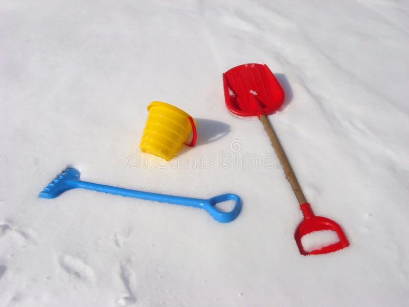 Kinderwinter-Spielgegenstände Eimer, Rührstange und Schaufel auf einem Schnee stockbilder