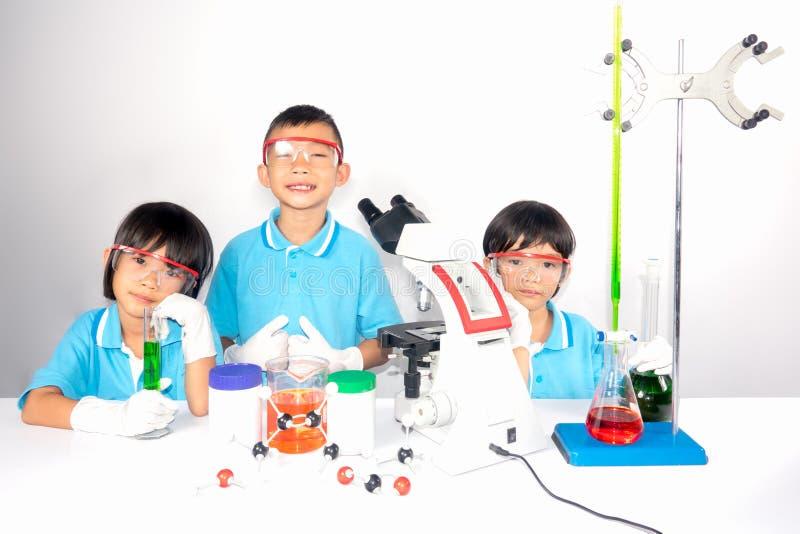 Kinderwissenschaft, die in der Schule auf weißem Hintergrund sich lehnt lizenzfreie stockfotos