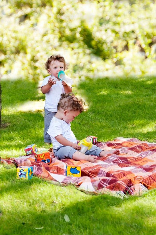 Kinderzwillings-Getränkwasser von einer Flasche stockbilder