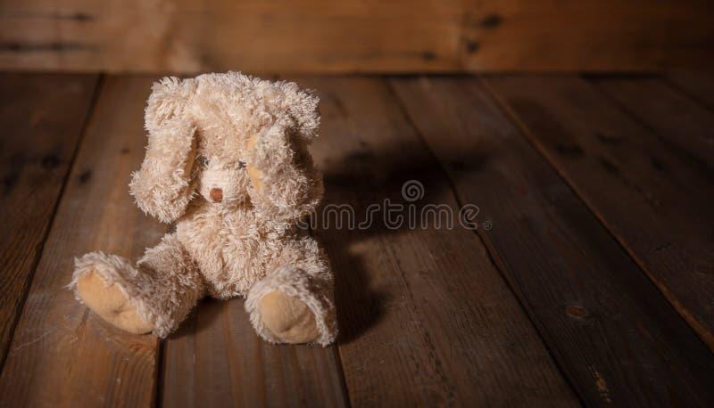 Kindesmissbrauch Teddybär, der Augen, dunklen leeren Hintergrund, Kopienraum bedeckt lizenzfreie stockbilder