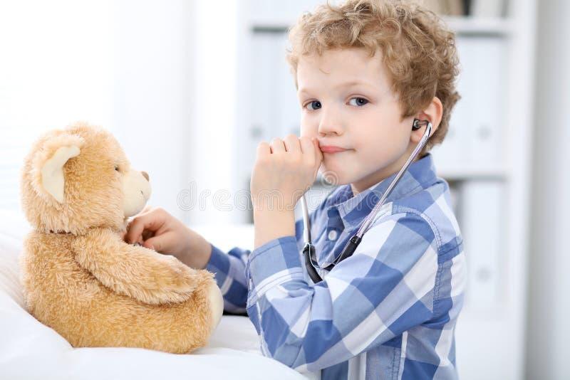 Kindgeduldige afrer Gesundheitsprüfung, die als Doktor mit Stethoskop und Teddybären spielt stockbild