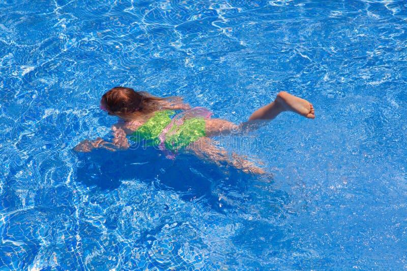 Kindgilr, das underwater im blauen Pool schwimmt lizenzfreie stockbilder