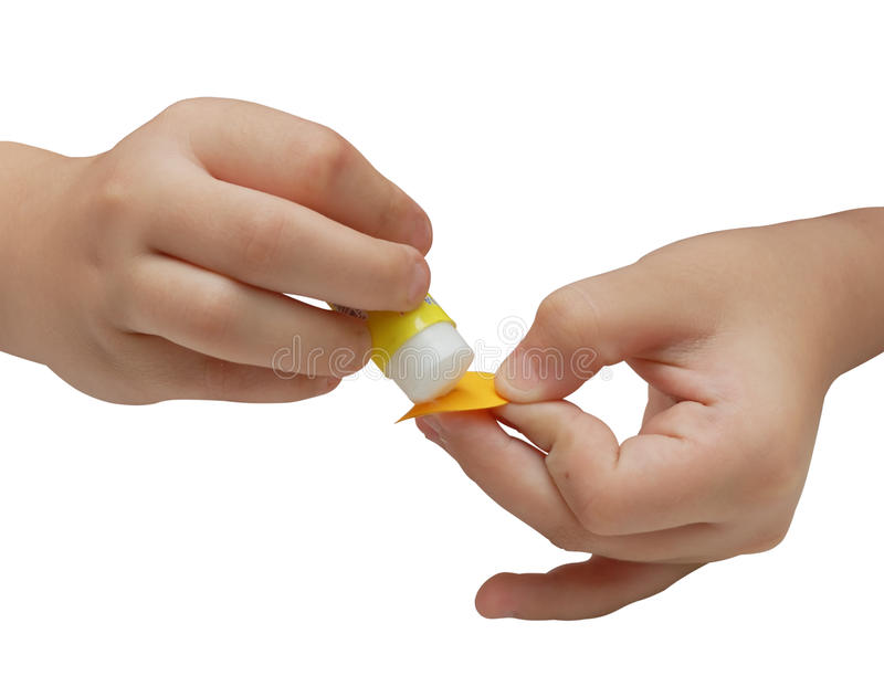 Kindhände tragen Kleber auf einem Papier auf lizenzfreies stockbild