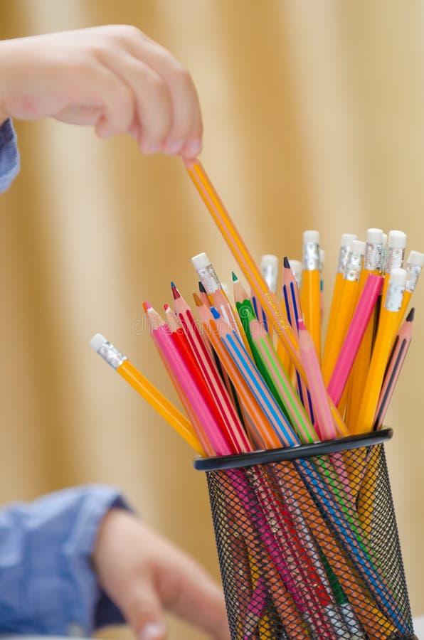 Kindhand en kleurpotlood royalty-vrije stock afbeelding