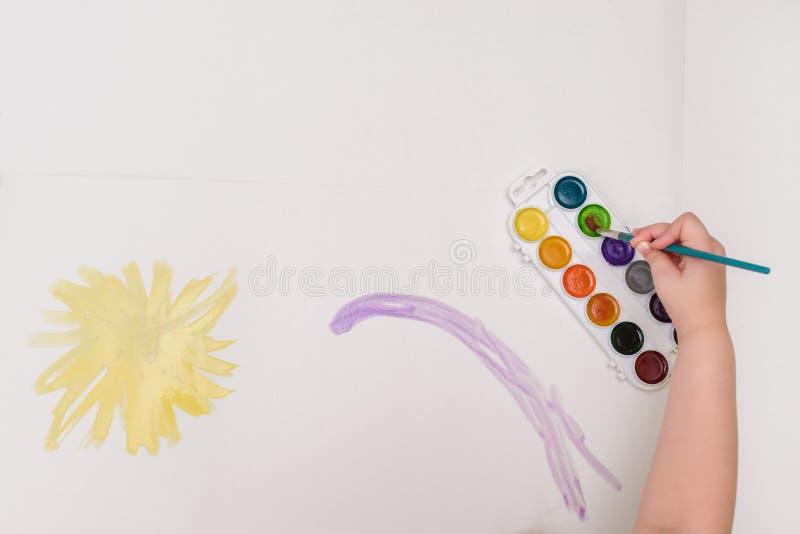 Kindhand met borstels die op Witboek gele zon trekken stock afbeeldingen
