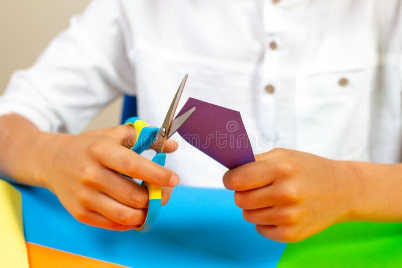 Kindhanden die gekleurd document met schaar snijden bij de lijst royalty-vrije stock foto's