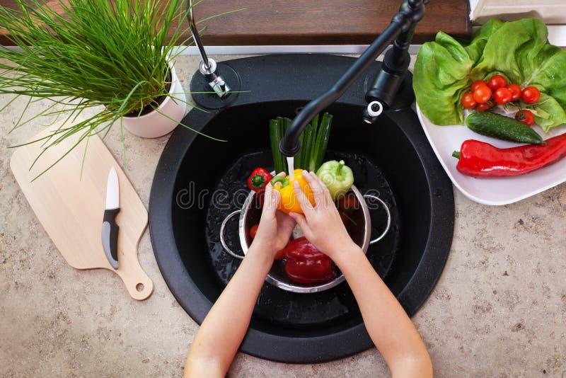 Kindhanden die groenten wassen bij de keukengootsteen - een bellpeppe royalty-vrije stock afbeelding