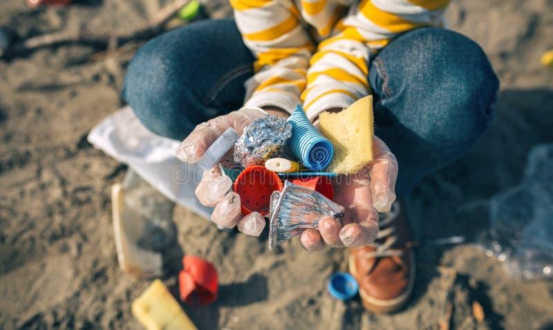 Kindhanden met huisvuil van het strand stock afbeelding
