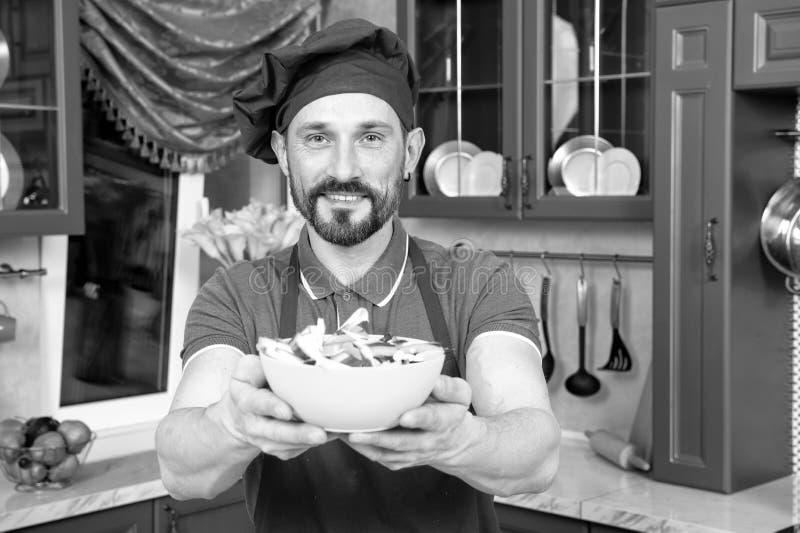 Kindhearted zadowolony kucharz oferuje puchar vitaminic sałatka obraz royalty free