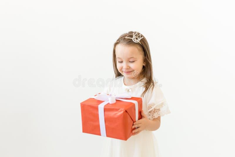 Kindheit, Kinder und Feiertagskonzept - kleines Mädchen im weißen Kleid mit Geschenkbox auf weißem Hintergrund stockfotos