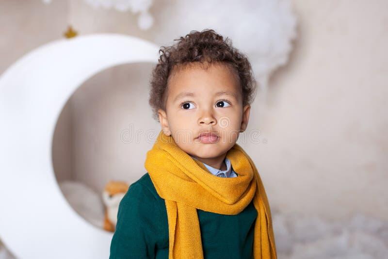 kindheit Schwarzer Jungenabschluß oben Porträt eines netten lächelnden Jungen in einem gelben Schal Porträt eines kleinen Afroame stockfoto