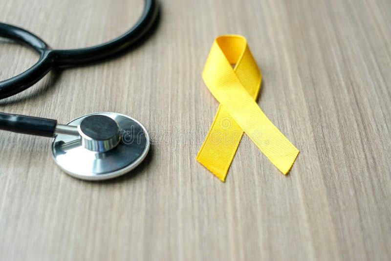 Kindheits-Krebs-Bewusstsein, gelbes Band mit Stethoskop für das Unterstützungsleuteleben lizenzfreies stockbild