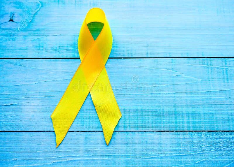 Kindheits-Krebs-Tag Gelbes Band auf blauem Hintergrund lizenzfreie stockbilder