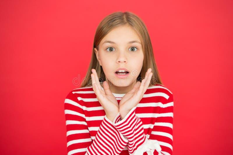 Kindheitsglück überrascht wenigem Mädchen auf rotem Hintergrund kleines Mädchenkind Schulbildung Familie und Liebe lizenzfreie stockfotografie