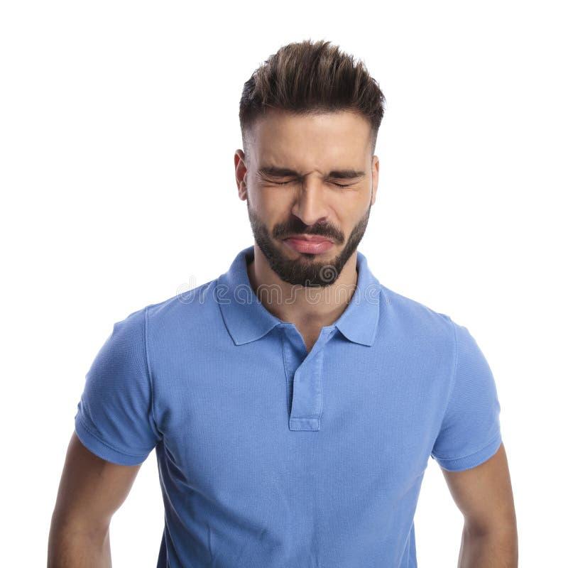 Kindischer junger Mann, der ein hellblaues Pologefühlsumkippen trägt lizenzfreies stockfoto