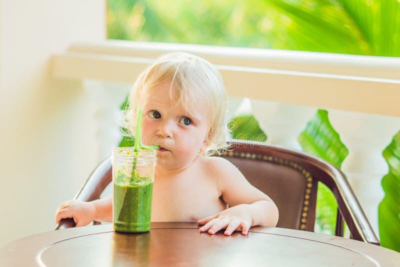 Kindjongen die gezonde groene plantaardige smoothie drinken - het gezonde eten, veganist, vegetariër, natuurvoeding en drankconce stock foto